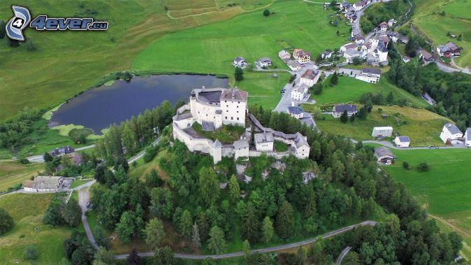 Burg Tarasp, Nadelbäume, See, Wiesen, Häuser