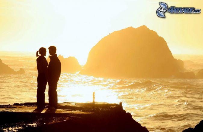 Paar am Meer, Klippe, Felsen im Meer, Sonnenuntergang