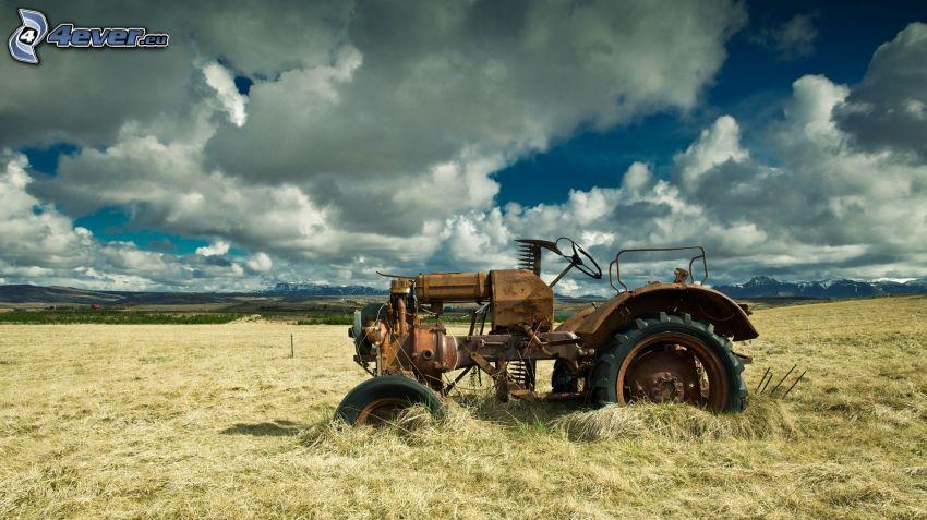 alter verlassenener Traktor, Wrack, Traktor auf dem Feld, Wolken
