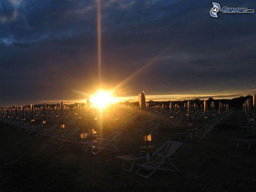 Sonnenuntergang über dem Strand, Liegestühle