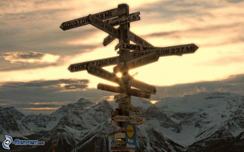 Wegweiser, schneebedeckte Berge, Sonnenuntergang in den Bergen
