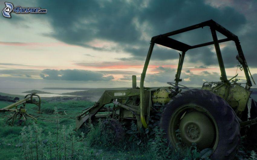 alter verlassenener Traktor, Wrack, Wolken