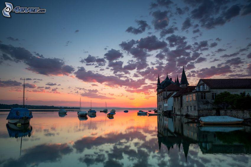 Haus am Ufer des Sees, Boote, orange Sonnenuntergang, Wolken