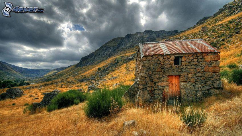 Häuschen, felsige Berge, dunkle Wolken, HDR