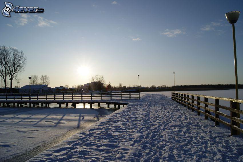 Holzsteg, gefrorener See, Schnee