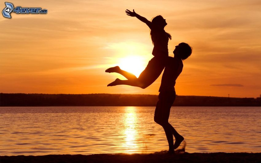 Abhebung beim See, Silhouette des Paares, Sonnenuntergang über dem See, orange Himmel
