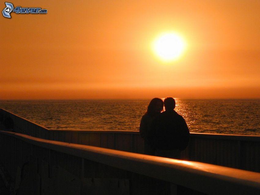 Orange Sonnenuntergang über dem Meer, Silhouette des Paares, Romantik