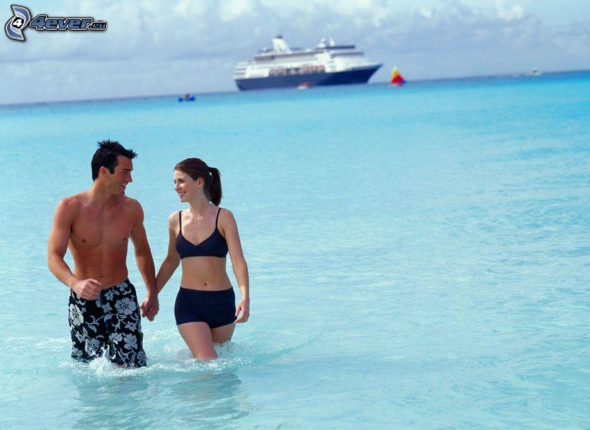 Paar im Meer, halten sich die Hände, Ausflugsschiff