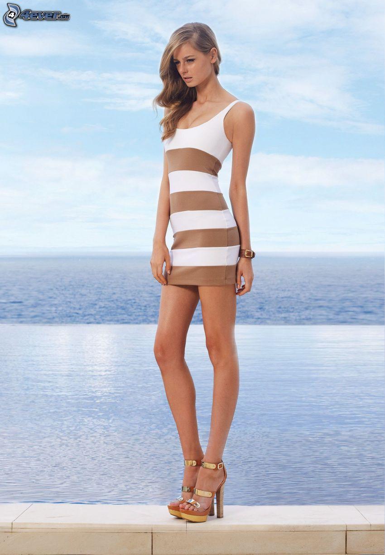 Brooke Daniels, beiges Kleid, schlanke Frau, Blick auf dem Meer, lange Beine
