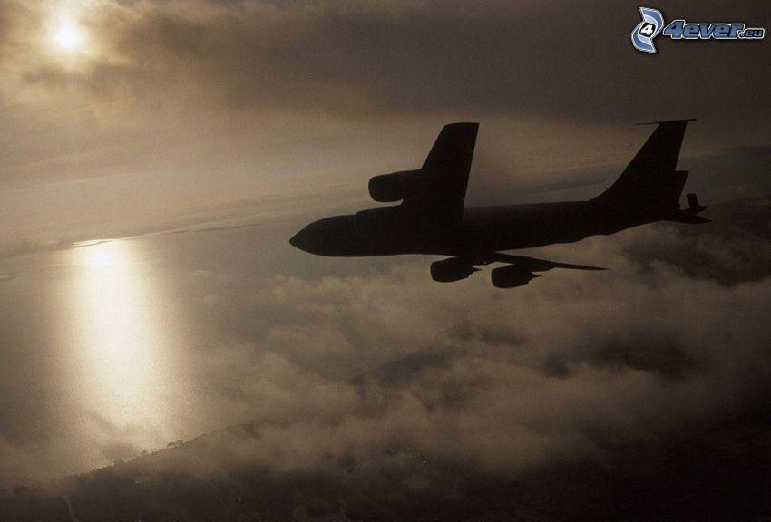 Silhouette des Flugzeuges, über den Wolken
