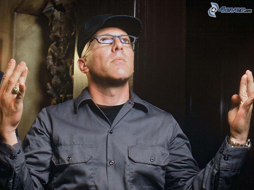 Maynard James Keenan, Mann mit Brille, Baseballcap, Geste