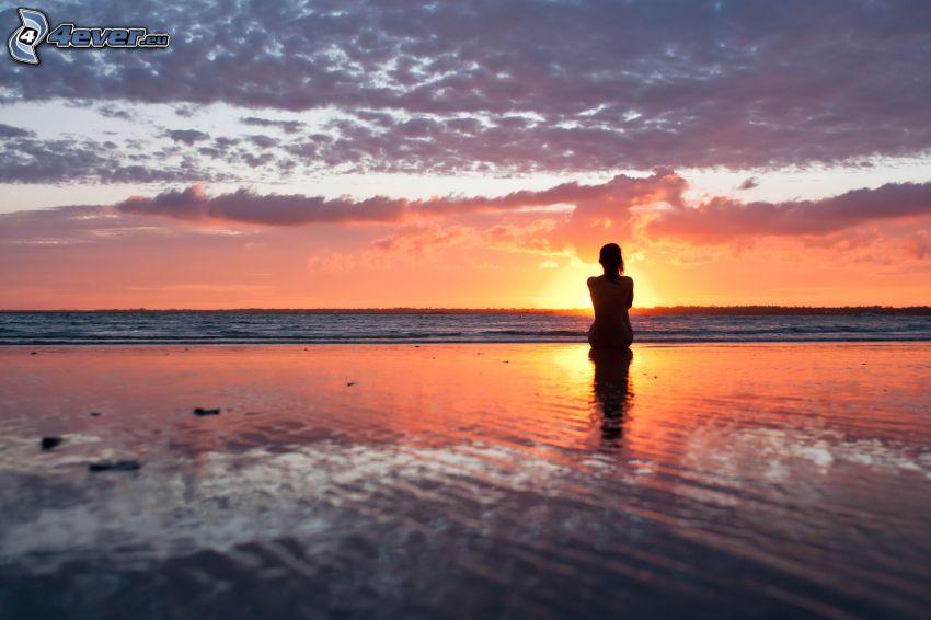 silhouette der Frau beim Sonnenuntergang, Strand, Abendhimmel