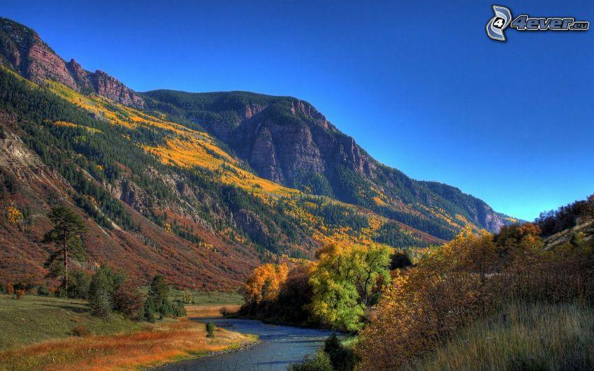 Berge, Fluss, bunter herbstlicher Wald