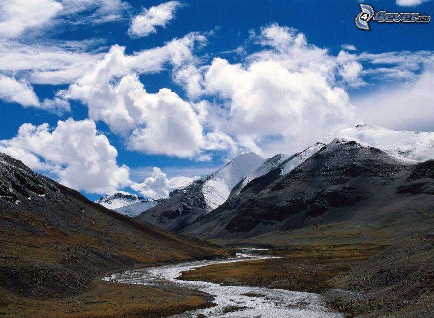 Gebirgsbach, schneebedeckte Berge, Wolken