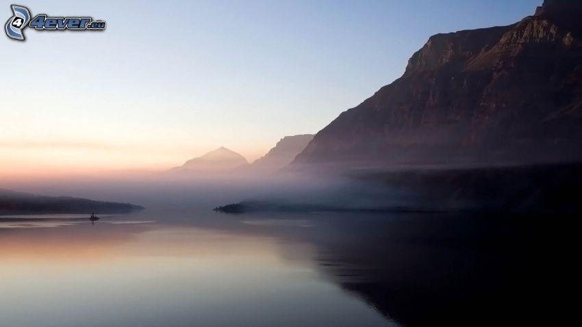See, nebliger Morgen, felsige Berge