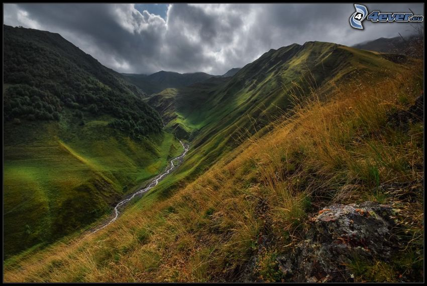Tal, hohe Berge, Fluss, trockenes Gras, Wolken