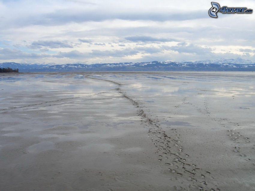 Fußspuren im Sand, schneebedeckte Berge