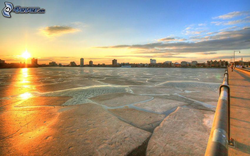 gefrorener Fluss beim Sonnenuntergang, Brücke, City