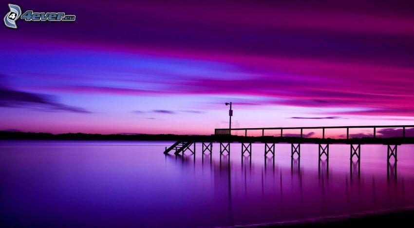 Holzsteg, abendlicher ruhiger See, lila Himmel