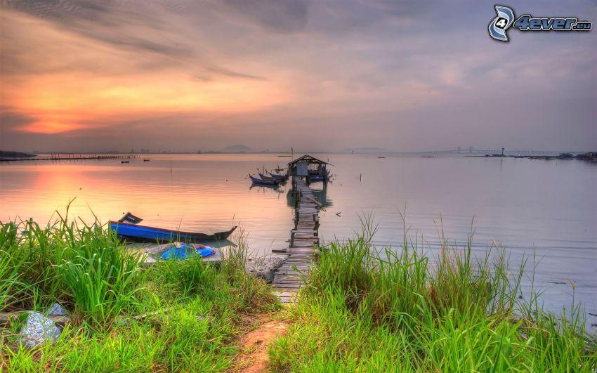 Holzsteg, verlassenes Boot, Sonnenuntergang über dem See, grünes Gras, Gras am Ufer des Sees
