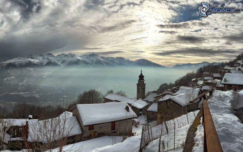 schneebedecktes Dorf, schneebedeckte Berge, Wolken