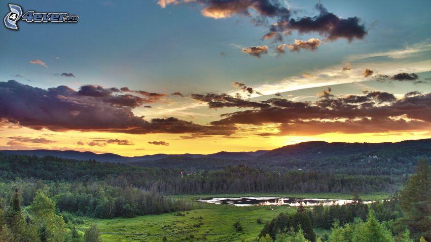 Sonnenuntergang hinter den Bergen, Wolken, Hügel, Bäume, See im Wald