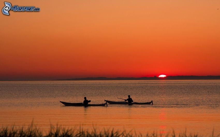 Kajak, Sonnenuntergang auf dem Meer, der rote Himmel