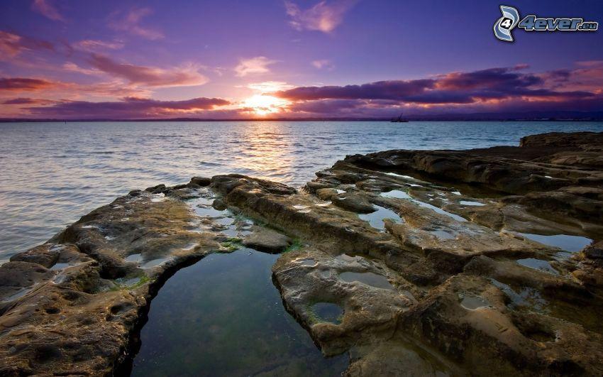 kaskadenförmige Küste, Sonnenuntergang auf dem Meer, lila Himmel