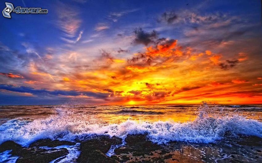 Orange Sonnenuntergang über dem Meer, stürmisches Meer