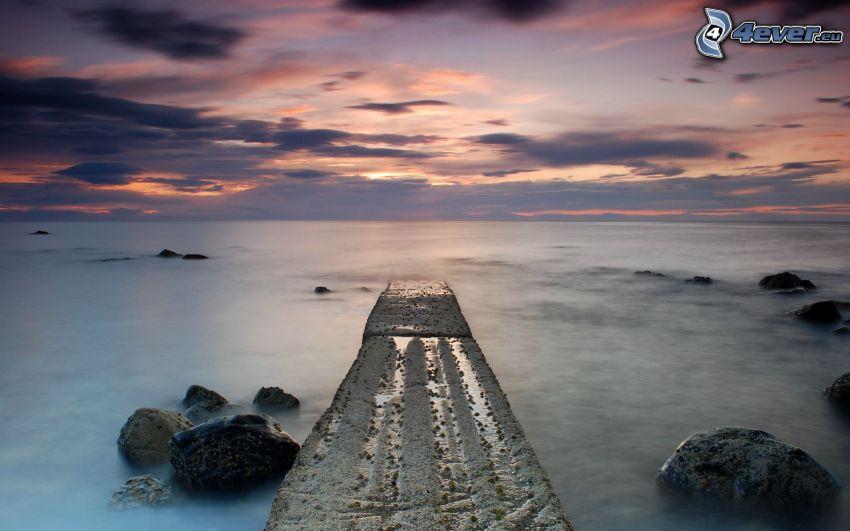 Pier, Felsen im Meer, nach Sonnenuntergang