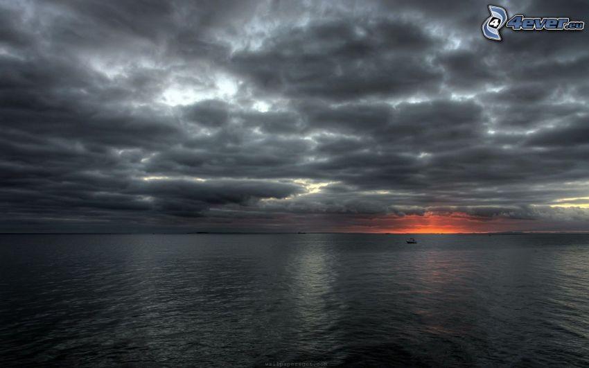 Sonnenuntergang auf dem Meer, dunkle Wolken, dunkles Meer