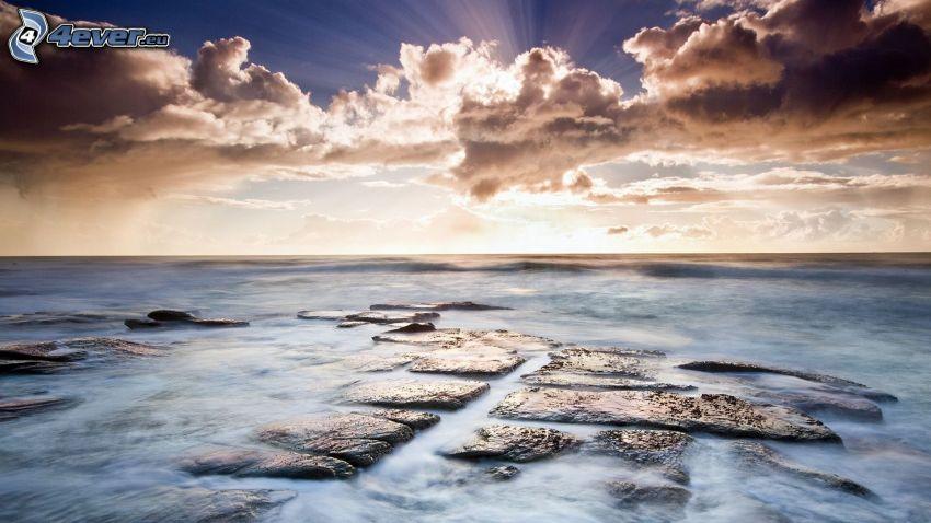 Sonnenuntergang über dem Meer, Sonne hinter den Wolken