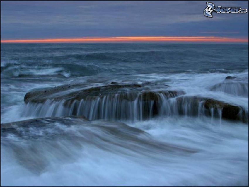 Steinstrand, Wellen, Felsen, Meer, nach Sonnenuntergang