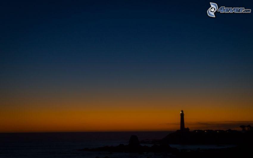 Strand nach dem Sonnenuntergang, Leuchtturm beim Sonnenuntergang