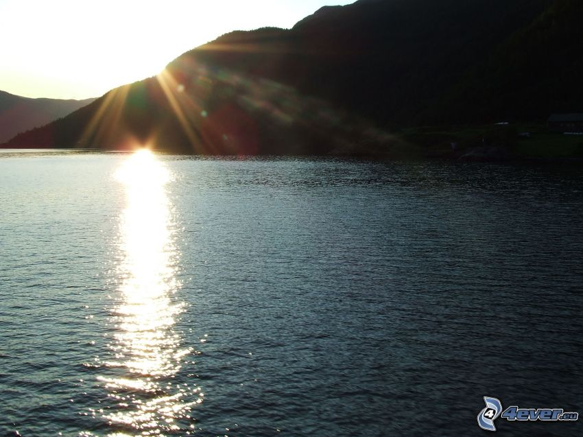 Sonne über dem See, Berg, Reflexion der Sonne