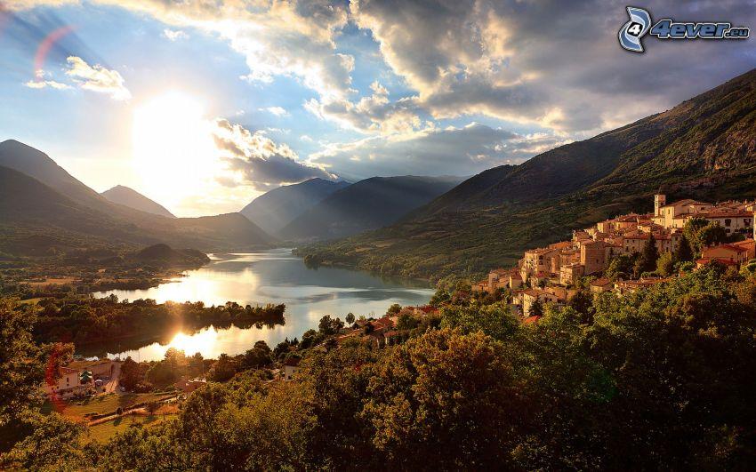 Sonne über dem See, Hügel, Häuser, Bäume, Aussicht auf die Landschaft