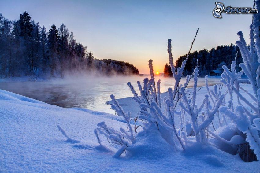 Sonnenuntergang über dem Fluss, verschneite Landschaft