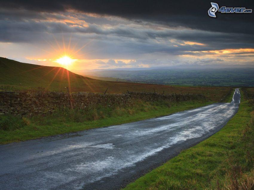 Weg, Sonnenuntergang hinter dem Hügel, dunkle Wolken