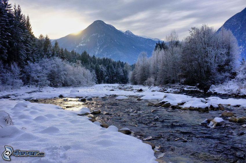 Winterlandschaft, Winterfluss, verschneiter Wald, Sonnenuntergang hinter den Bergen