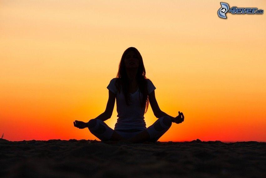 Meditation, Yoga, türkische Sitzung, Silhouette der Frau, orange Sonnenuntergang