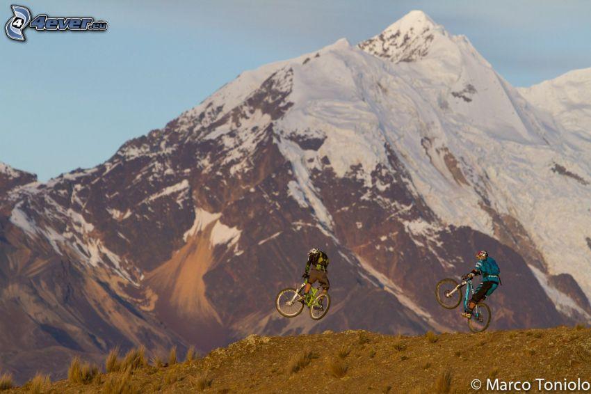 mountain biker, Sprung auf dem Fahrrad, schneebedeckte Berge