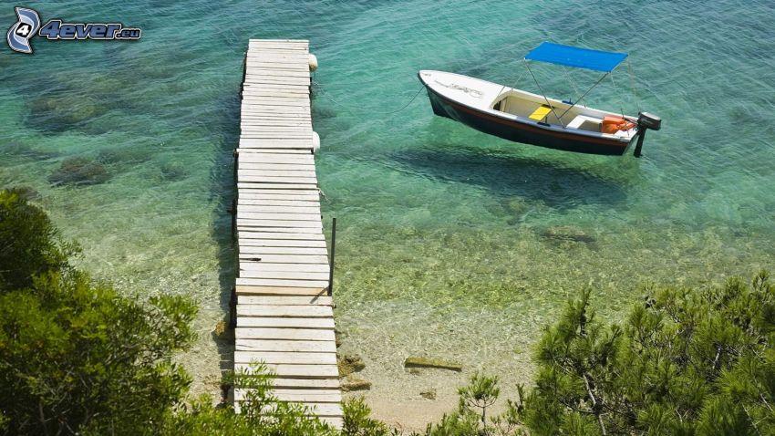 Boot am Ufer, Holzsteg, seichtes azurblaues Meer