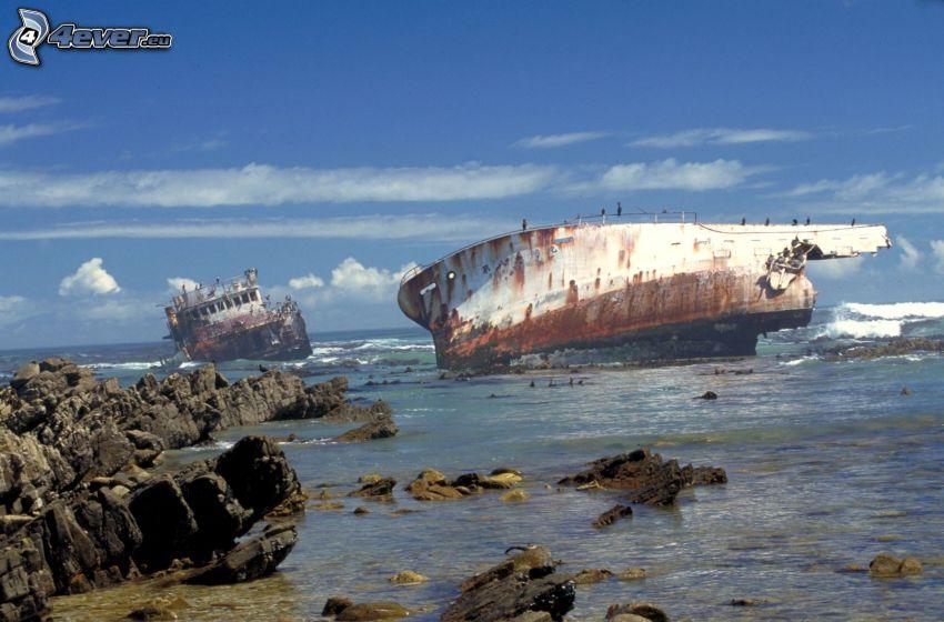 verlassenes rostiges Schiff, Wrack, Meer, felsige Küste