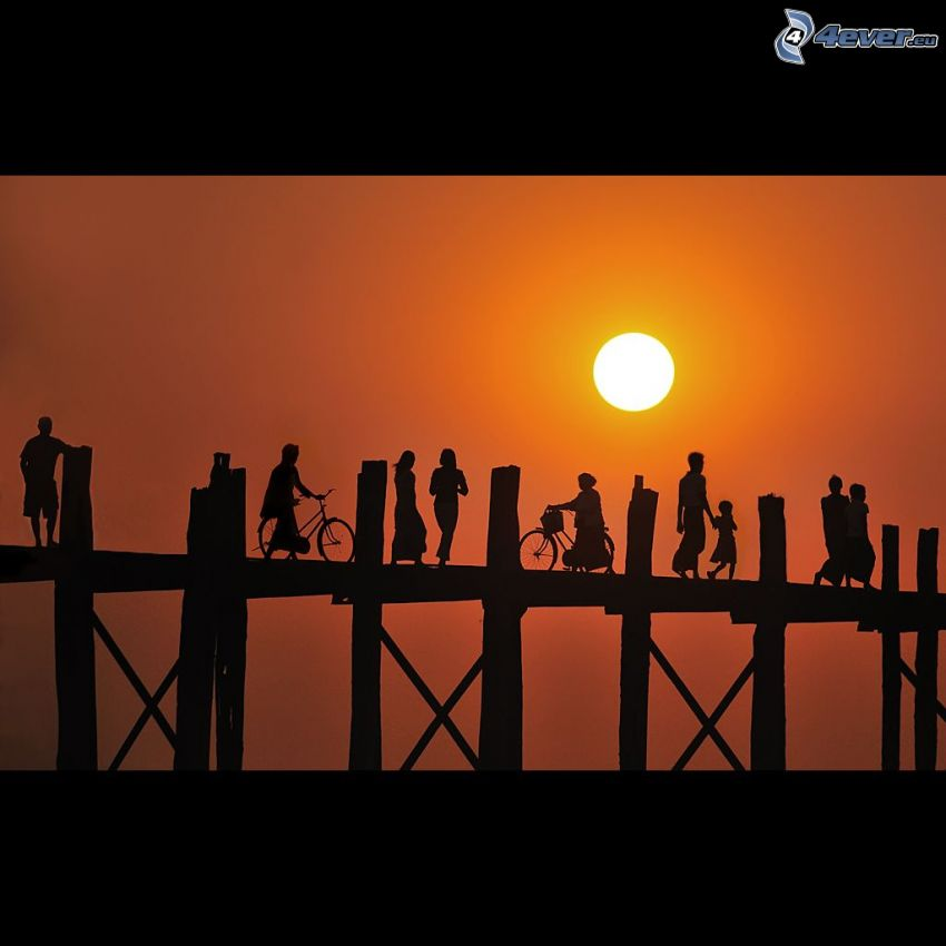 Holzsteg, Silhouetten von Menschen, Sonne, orange Himmel