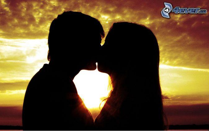 silhuett av ett par, puss, solnedgång