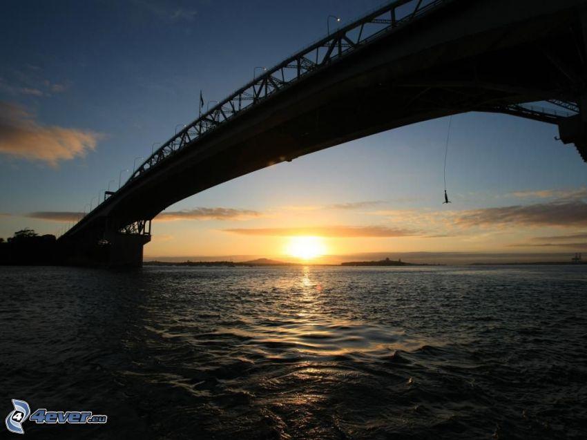 Auckland Harbour Bridge, solnedgång över havet