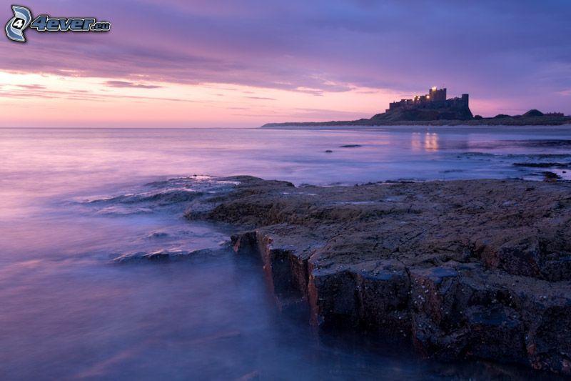 Bamburgh castle, lila himmel, öppet hav