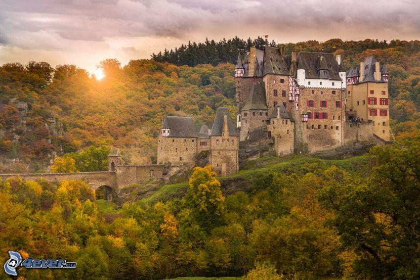 Eltz Castle, höstskog, solnedgång bakom skogen