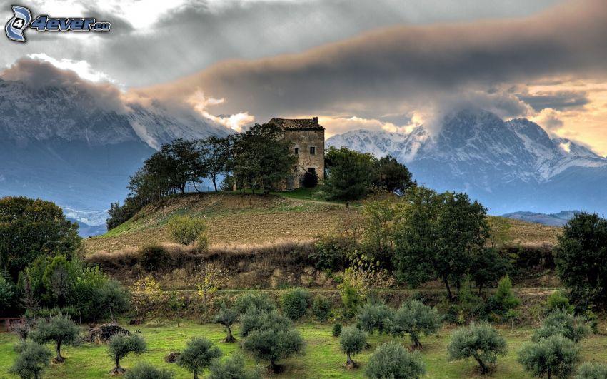 hus på kulle, snöklädda berg, moln