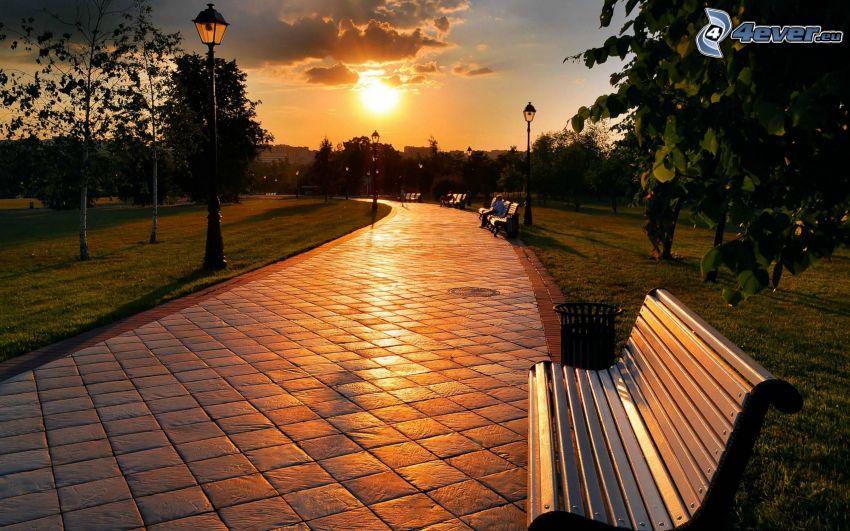park vid solnedgången, trottoar, bänkar, lampor